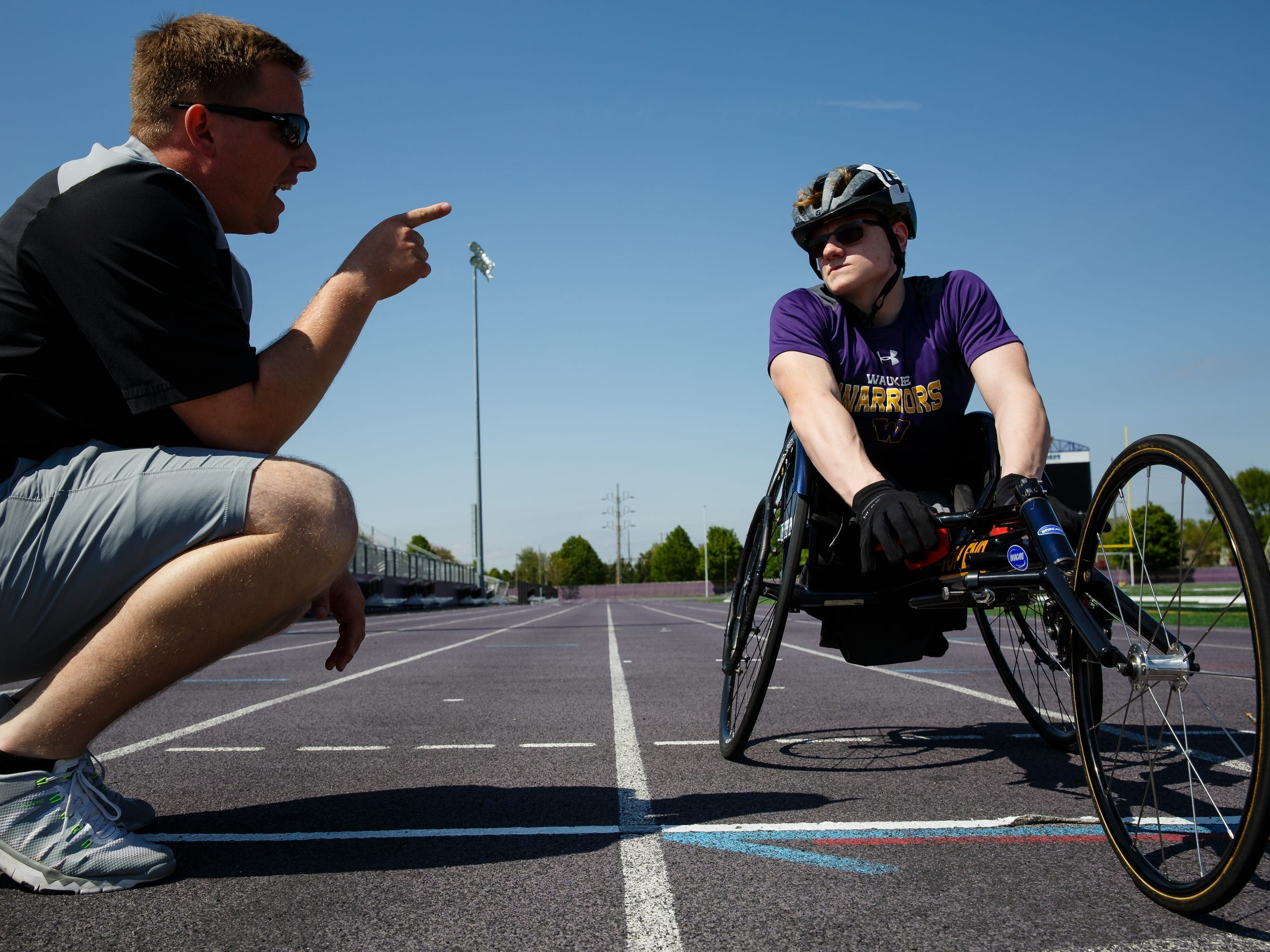 Working with assistant coach Gage Mohs, left, Evan Correll discusses strategy for the 800-meter race at Iowa's state track and field meet on Tuesday, May 14, 2019, in Waukee. For the first year Iowa is offering four track races to wheelchair athletes and Correll has a chance to win all of them.