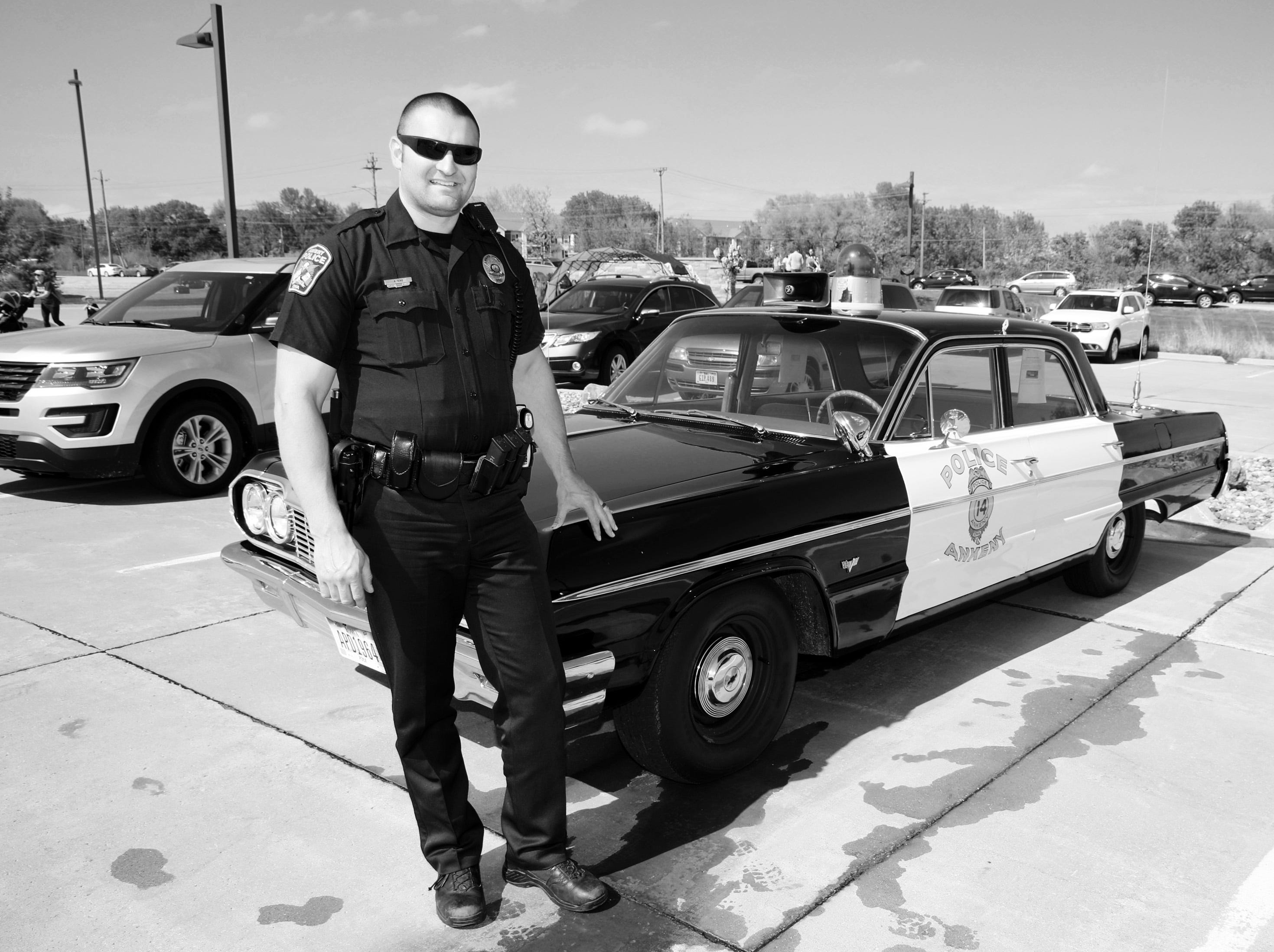 Officer Aaron King of the Ankeny Police Dept. stands by the classic 1964 police car during the Ankeny Police Week Community Picnic on Tuesday, May 14, 2019 at the Ankeny Police Headquarters located at 411 SW Ordnance Road. The event featured a tour of the police station, magician Jonathon May, free Chick Fil-A sandwiches for the first 1,000 guests, free Kona Ice, temporary tattoos, and a great opportunity to meet the officers who protect and serve the city of Ankeny.