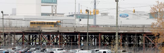 A school bus and other vehicles cross over the Miller Road Bridge in Dearborn on Thursday, April 2, 2019. The bridge has hundreds of temporary supports.
