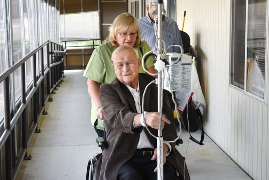 Oakland County Executive L. Brooks Patterson pushes his IV pole as he is wheeled down a corridor heading for his evaluation for cancer treatment assisted by Patricia O'Brien at the Karmanos Cancer Institute in Farmington Hills.