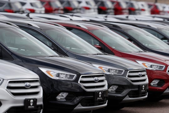 In this Feb. 17, 2019, file photo rows of unsold 2019 Escape sports-utility vehicles sit in long rows at a Ford dealership in Broomfield, Colo.
