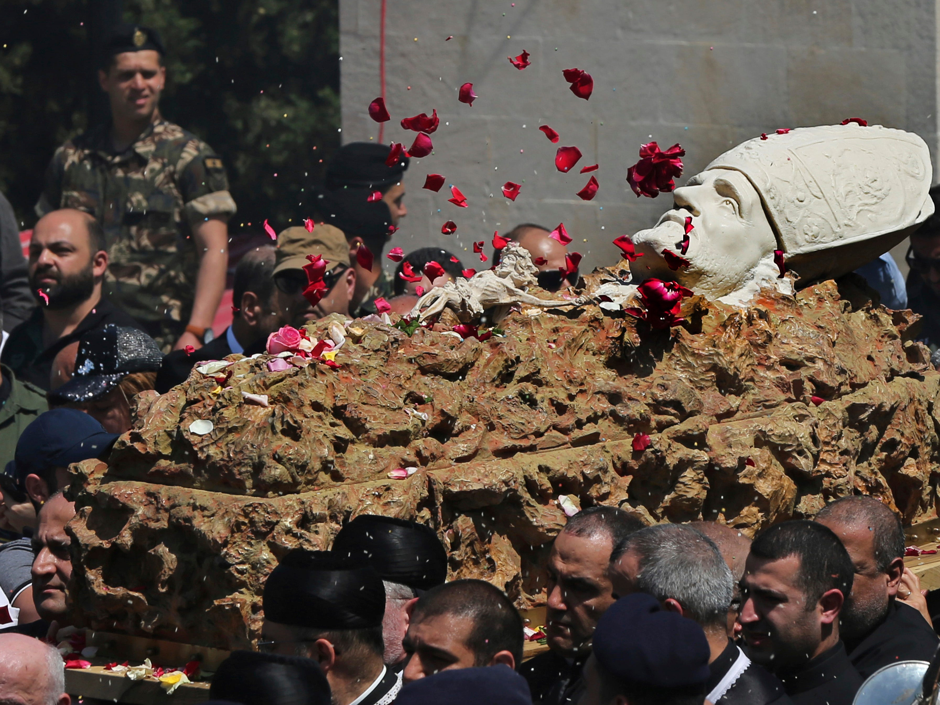 Mourners throw flowers on the coffin of former Maronite Patriarch Cardinal Mar Nasrallah Boutros Sfeir, as it arrived at the seat of the Maronite Church, in the village of Bkirki, north of Beirut, Lebanon, Wednesday, May 15, 2019. Sfeir, who served as spiritual leader of Lebanon's largest Christian community through some of the worst days of the country's 1975-1990 civil war, died Sunday and his funeral will take place Thursday May 16.