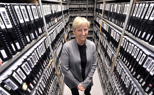 Cindy Olmstead, CEO of The Michigan Braille Transcribing Fund, stands in the master library of tactile graphics, with more than 4,000 titles, at the G. Robert Facility in Jackson.