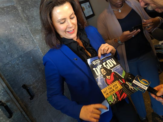 "Michigan Gov. Gretchen Whitmer holds up a logo for ""The Gov"" beer at Lansing Brewing Company on May 14, 2018."