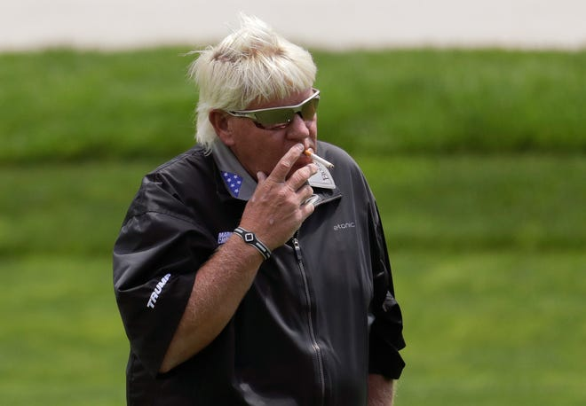 John Daly smokes a cigarette on the ninth hole during a practice round.