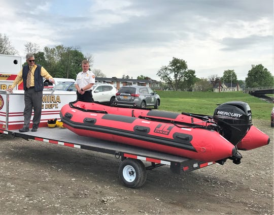 Chemung River Friends Executive Director Jim Pfiffer, left, points out some of the features of a new river rescue boat, as Elmira Fire Chief Joseph Martino looks on.