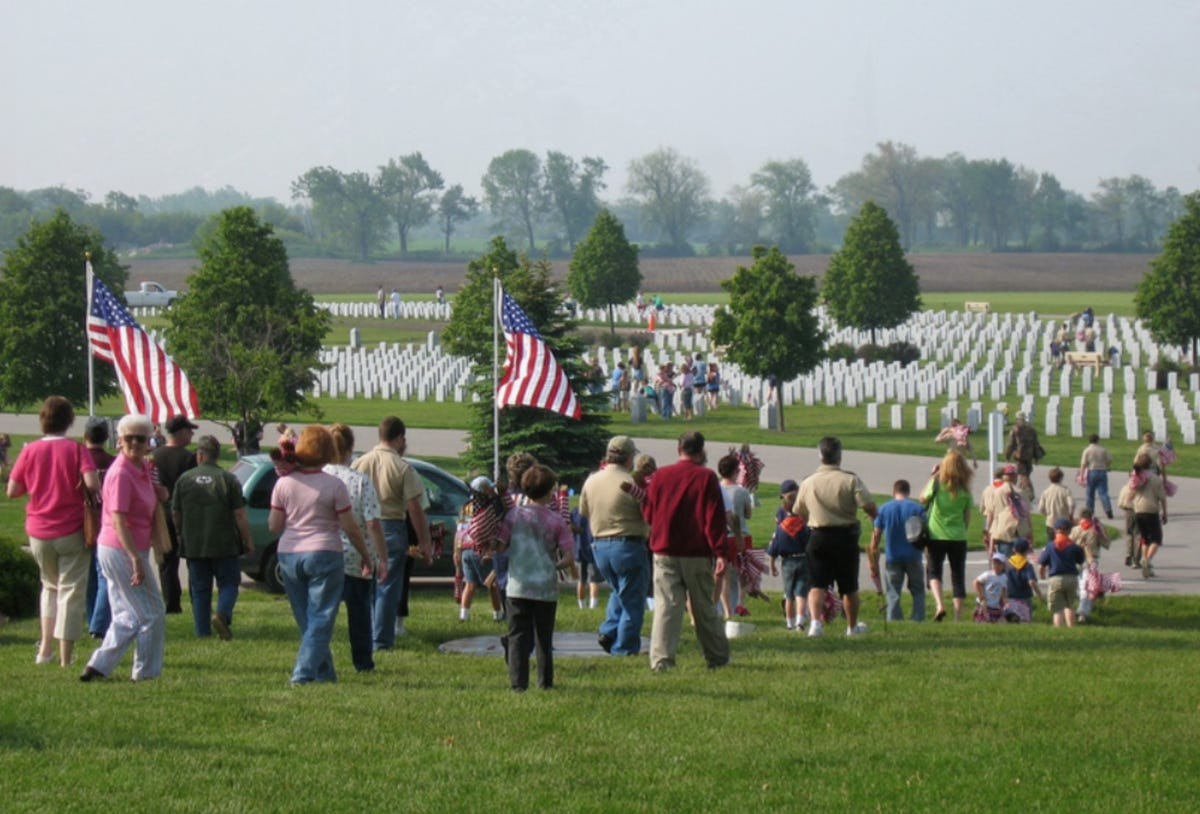 Who places flags on veterans' graves for Memorial Day?