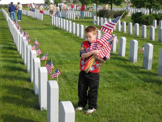 A young Boy Scout pauses at the grave of a military veteran buried at  Southern Wisconsin Veterans Memorial Cemetery in Union Grove during a Flags-in event,  held prior to Memorial Day.