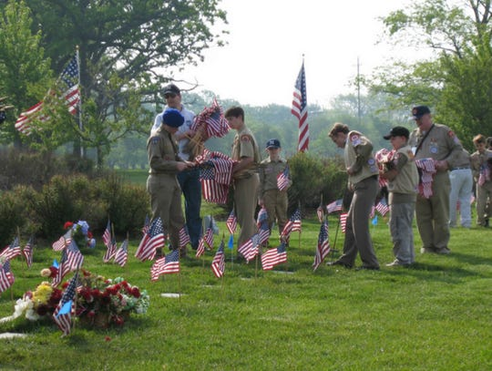 A group of Boy Scouts place flags on the graves of military veterans during a Flags-In event held at Southern Wisconsin Veterans Memorial Cemetery in Union Grove. The flags are placed each year prior to the Memorial Day weekend.
