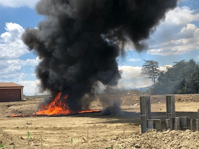 A plume of black smoke and flames cover the site of a plane crash Wednesday near the Northern Colorado Regional Airport.