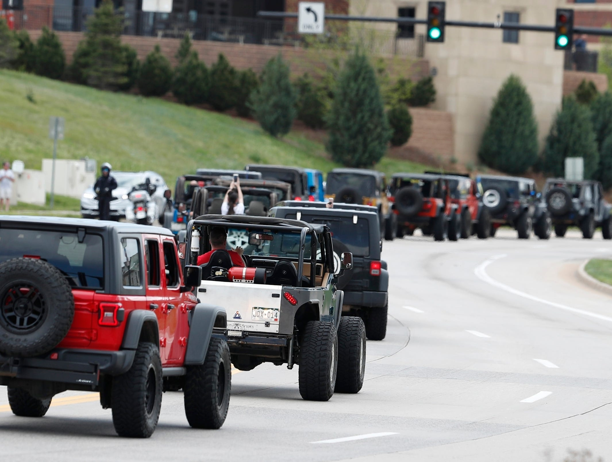 More than 600 Jeeps lead a caravan Wednesday, May 15, 2019 to the memorial service for Kendrick Castillo, who was killed in the assault on the STEM Highlands Ranch School, in Highlands Ranch, Colo.