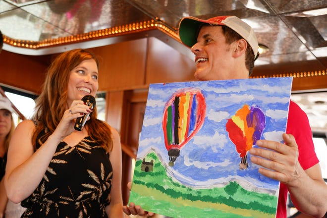 """Soap stars Melissa Archer and Christian LeBlanc auction a kid's original painting during the 2018 SoapFest's """"Booze Cruise"""" to raise funds for local children charities"""