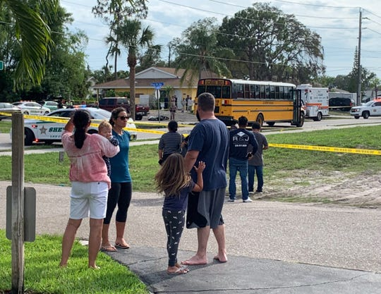 Residents along Pennsylvania Avenue in Bonita Springs watch Florida Highway PAtrol troopers investigate a fatal   motorcycle crash. The motorcyclist crashed into the rear bumper of a Lee County School bus shortly before 4:30 p.m. Wednesday.
