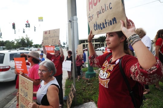 Hannah Stoneman, a teacher at Village Oaks in Immokalee, protests with other educators and concerned citizens in front of the Collier County Courthouse on Wednesday, May 15, 2019. They were protesting several topics including low wages and gun violence in schools.
