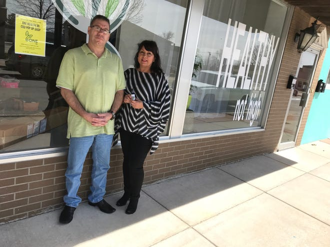 """A window sign says """"Healthy not high"""" at One Health Wisconsin, where Mike Swille and Stacey Deprey-Purper sell CBD oils and other natural health products."""