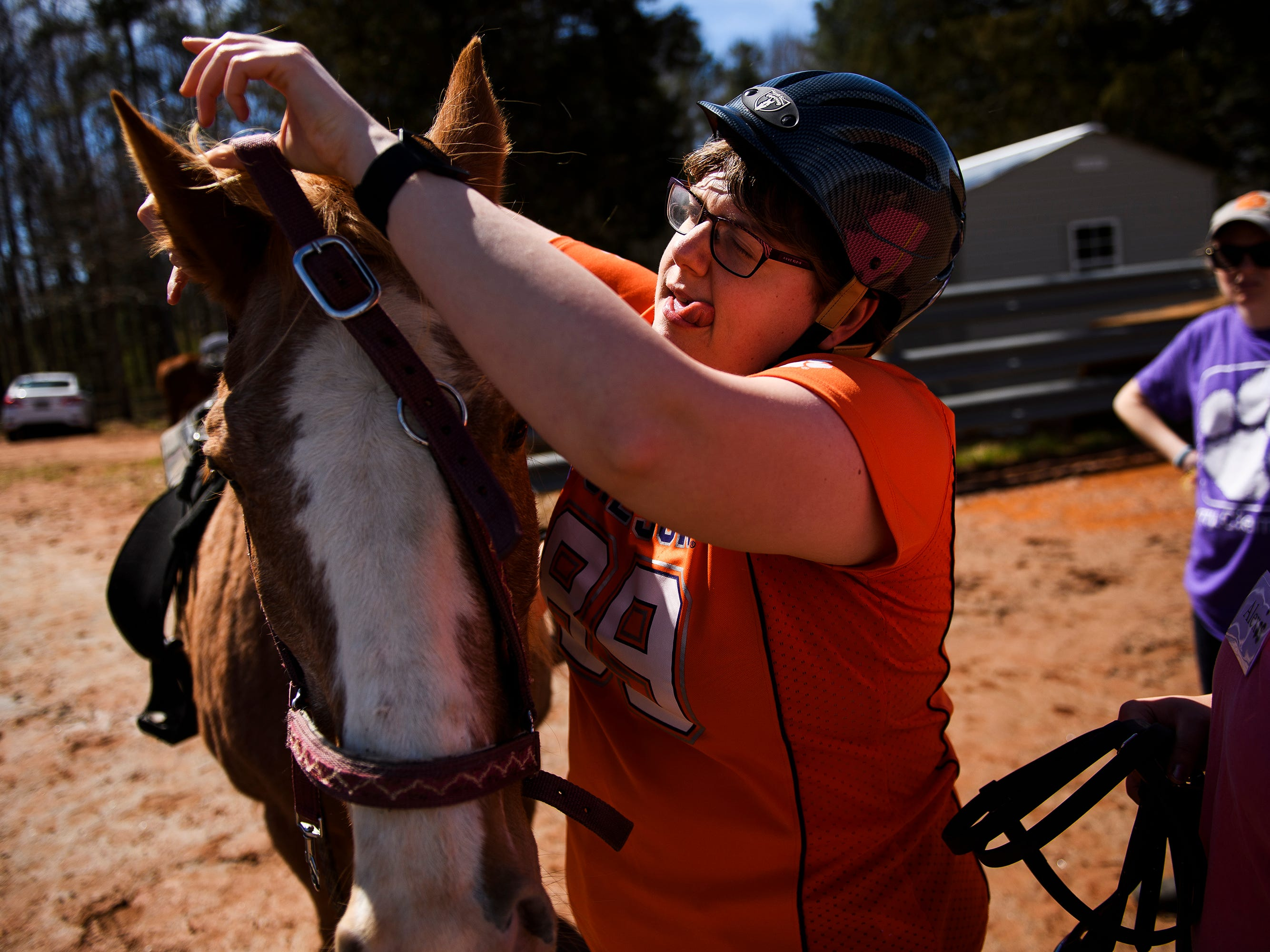 Sarah Wright, 29, adjusts the harness on a horse during a riding lesson at J Rest Farm Tuesday, March 12, 2019.
