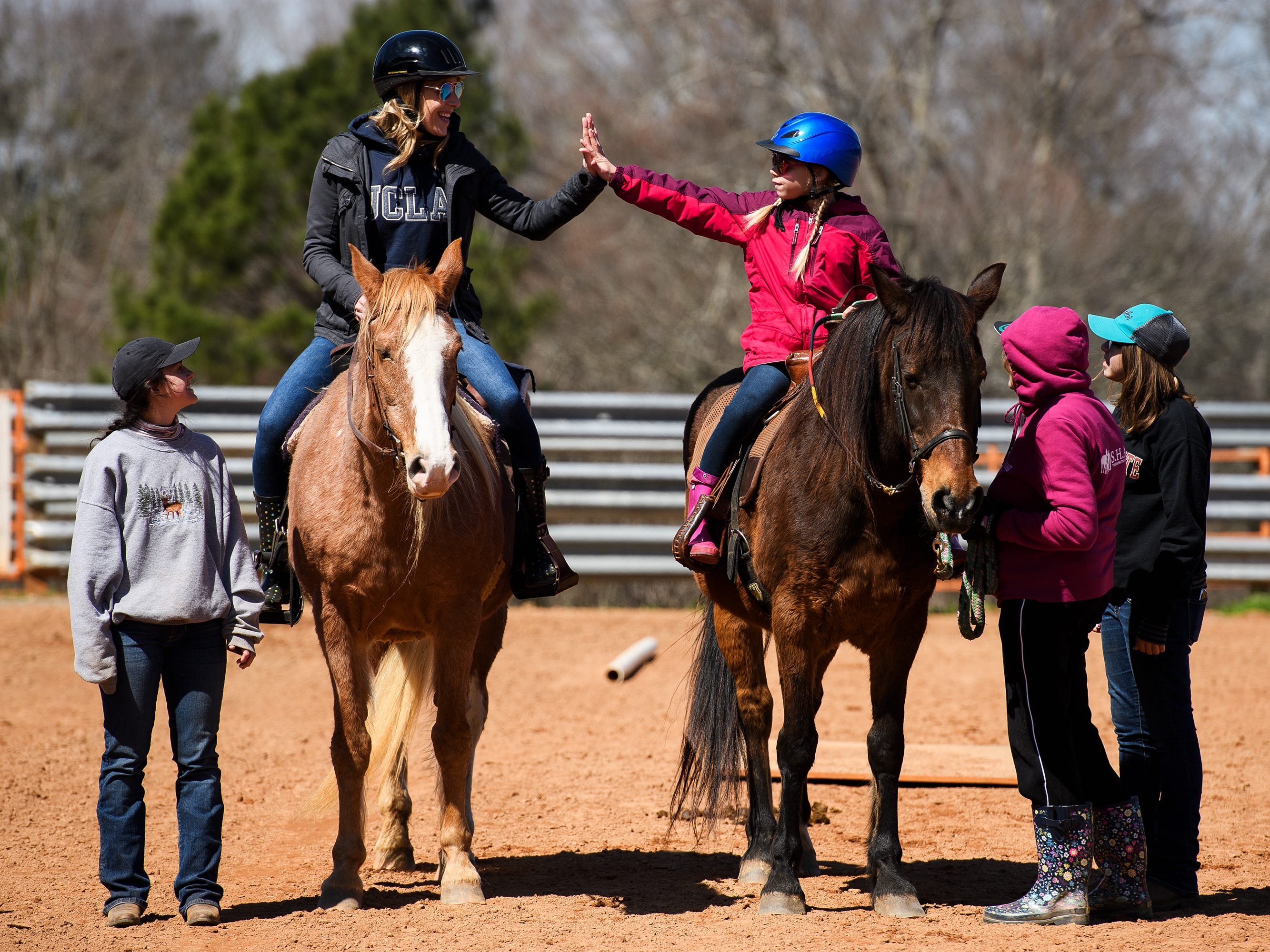 Madison Young, 10, high fives her mother, Katie Young, during a riding lesson at J Rest Farm, Tuesday, March 19, 2019.