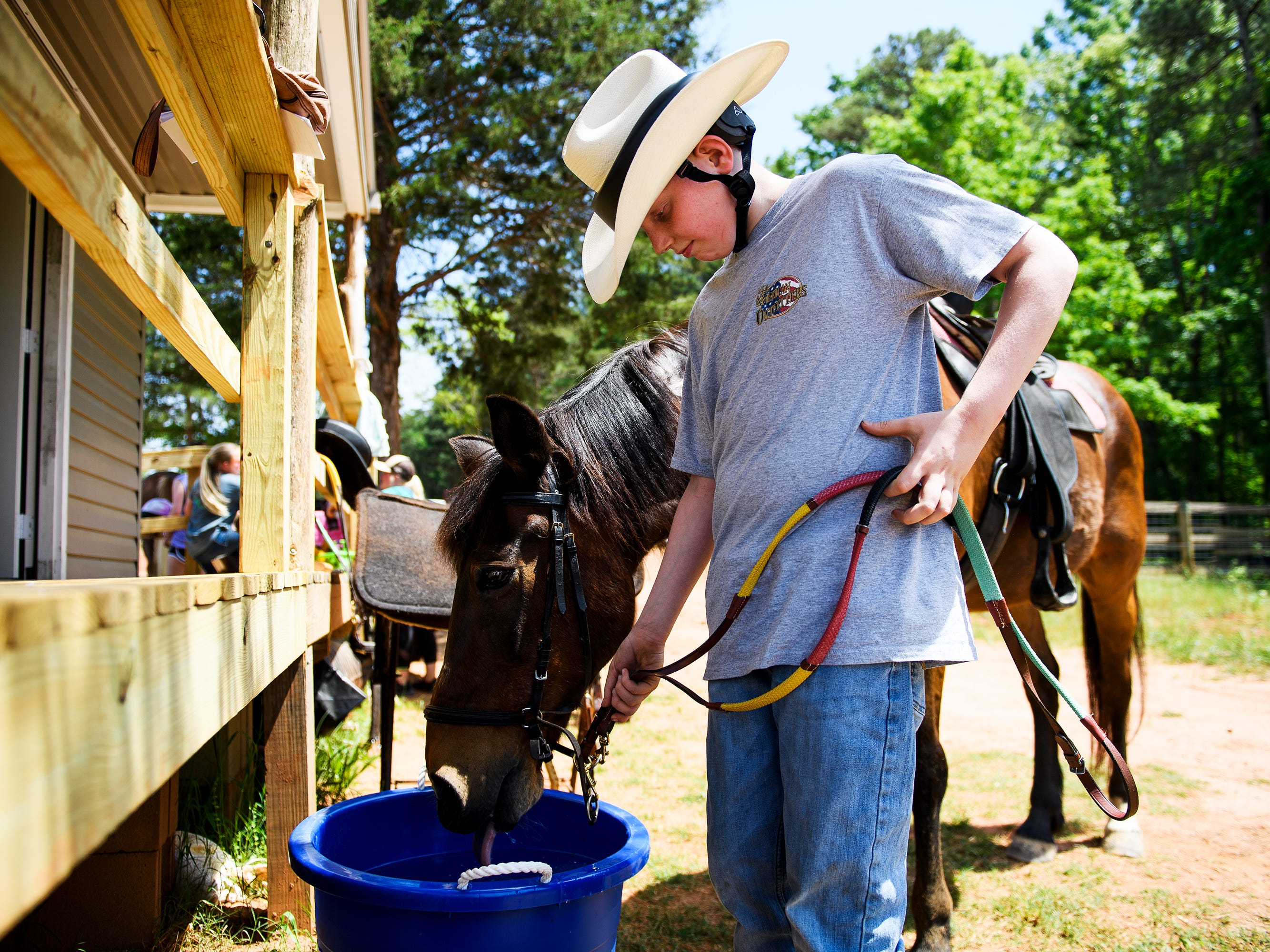 Logan Moore walks a horse to a drinking bucket during his riding lesson at J Rest Farm, Tuesday, April 30, 2019.
