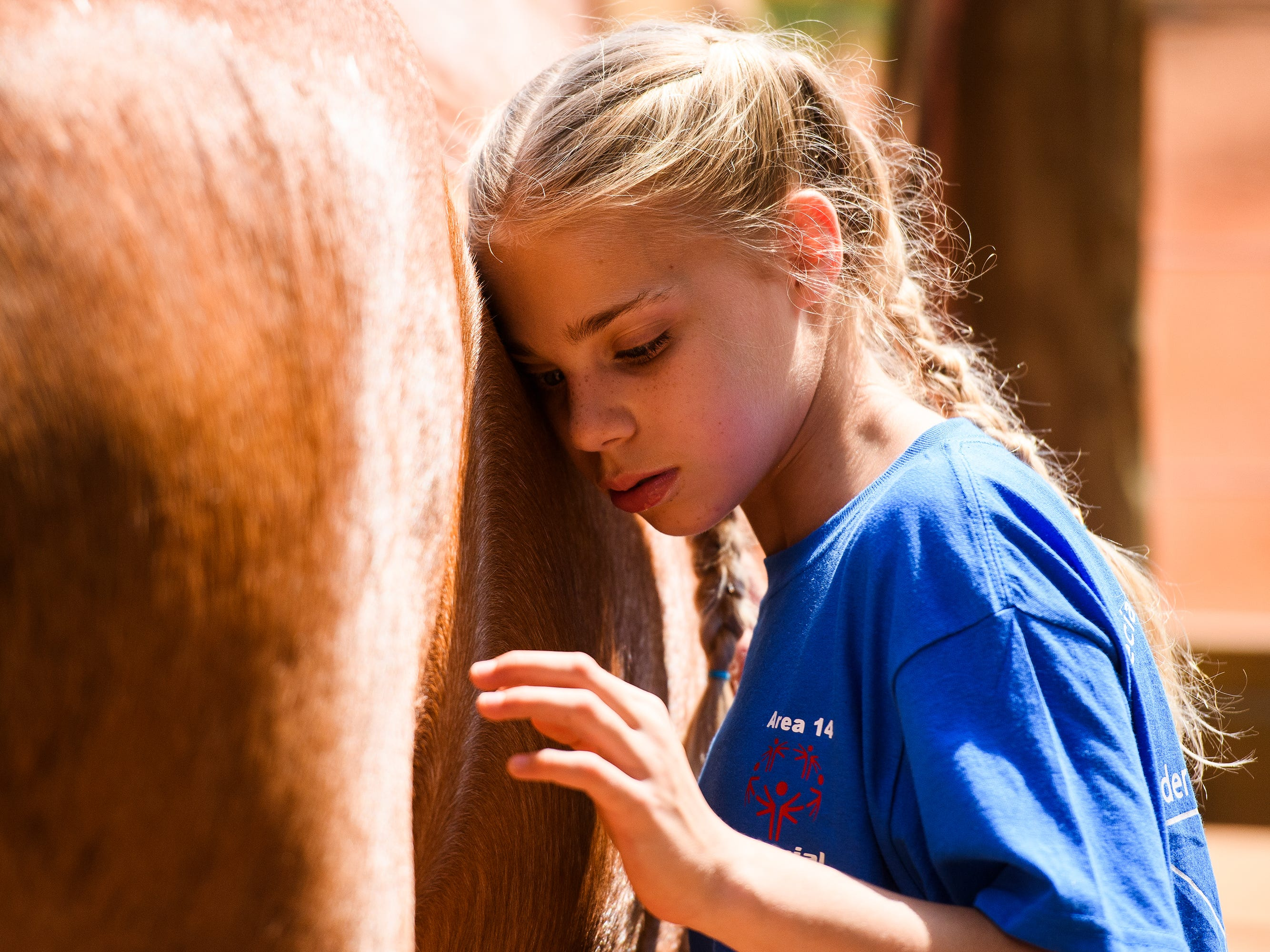 Madison Young, 10, listens to the rumblings of a horse's stomach the day of the S.H.A.R.E. therapeutic horse riding show at J Rest Farm in Anderson, Saturday, May 4, 2019. The show is the culmination of a 12-week program for children and adults with special needs. Students run through a course featuring a series of obstacles and, when they aren't on the saddle, learn how to groom and take care of the horses. Often, students develop deep bonds with the horses as they advance through the program.