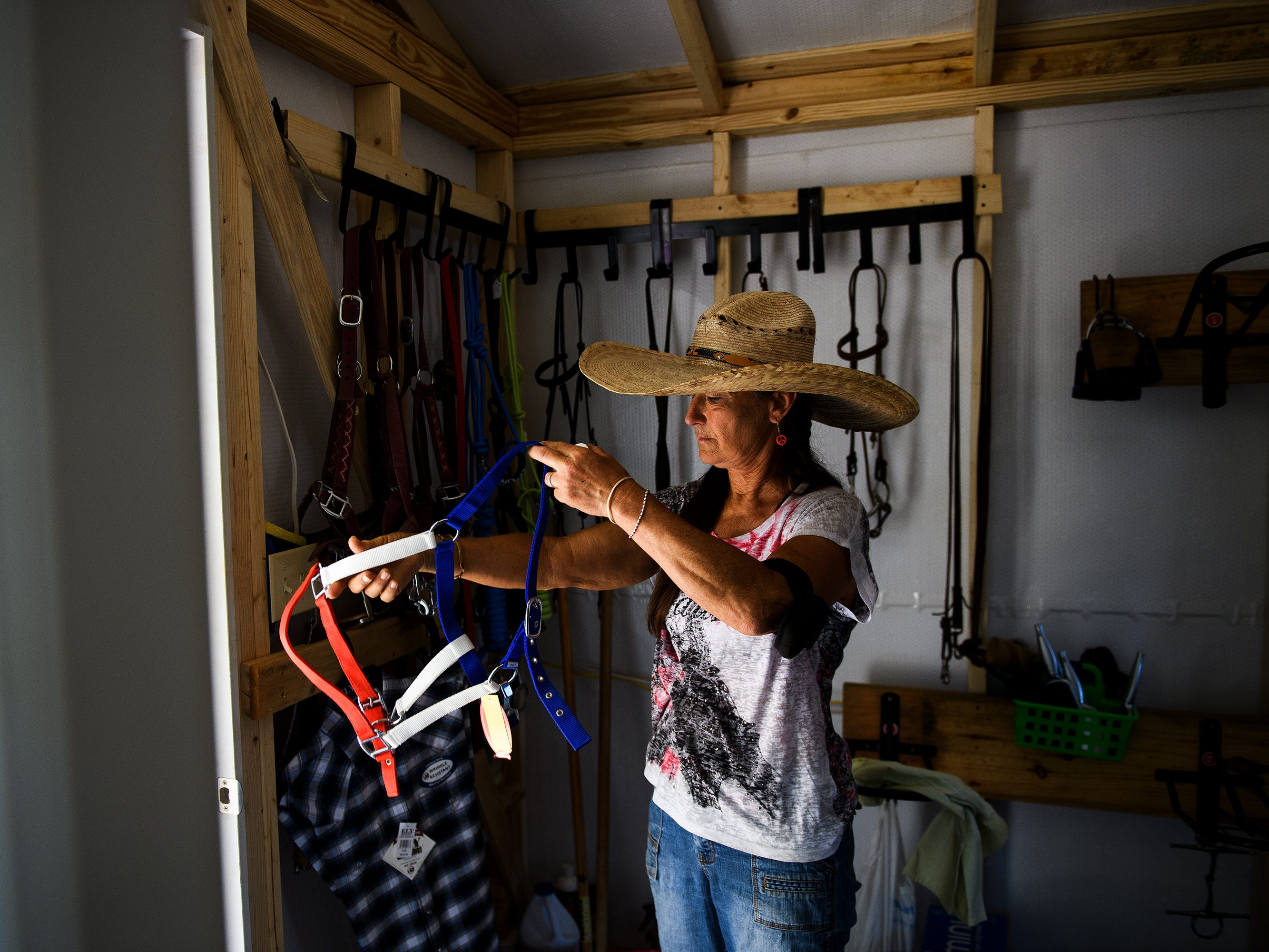 Lisa Hartman inspects a harness in the storage shed at J Rest Farm Tuesday, April 30, 2019.