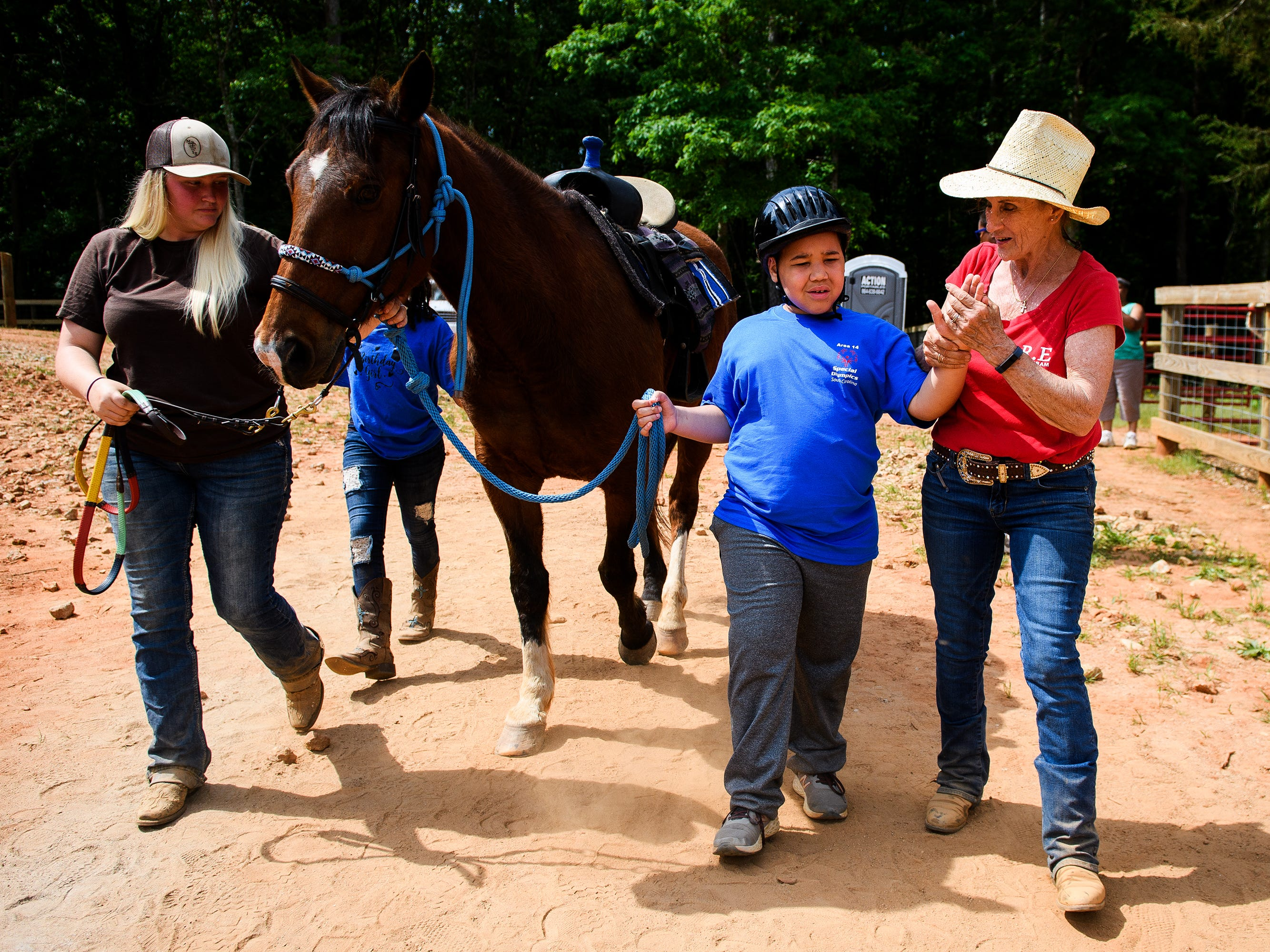 Justice Brown is assisted by volunteers Darlene Whitemore and Mara Harrison Todd as he makes his way to the obstacle course during a show day for students in the S.H.A.R.E. therapeutic riding program at J Rest Farm, Saturday, May 4, 2019.