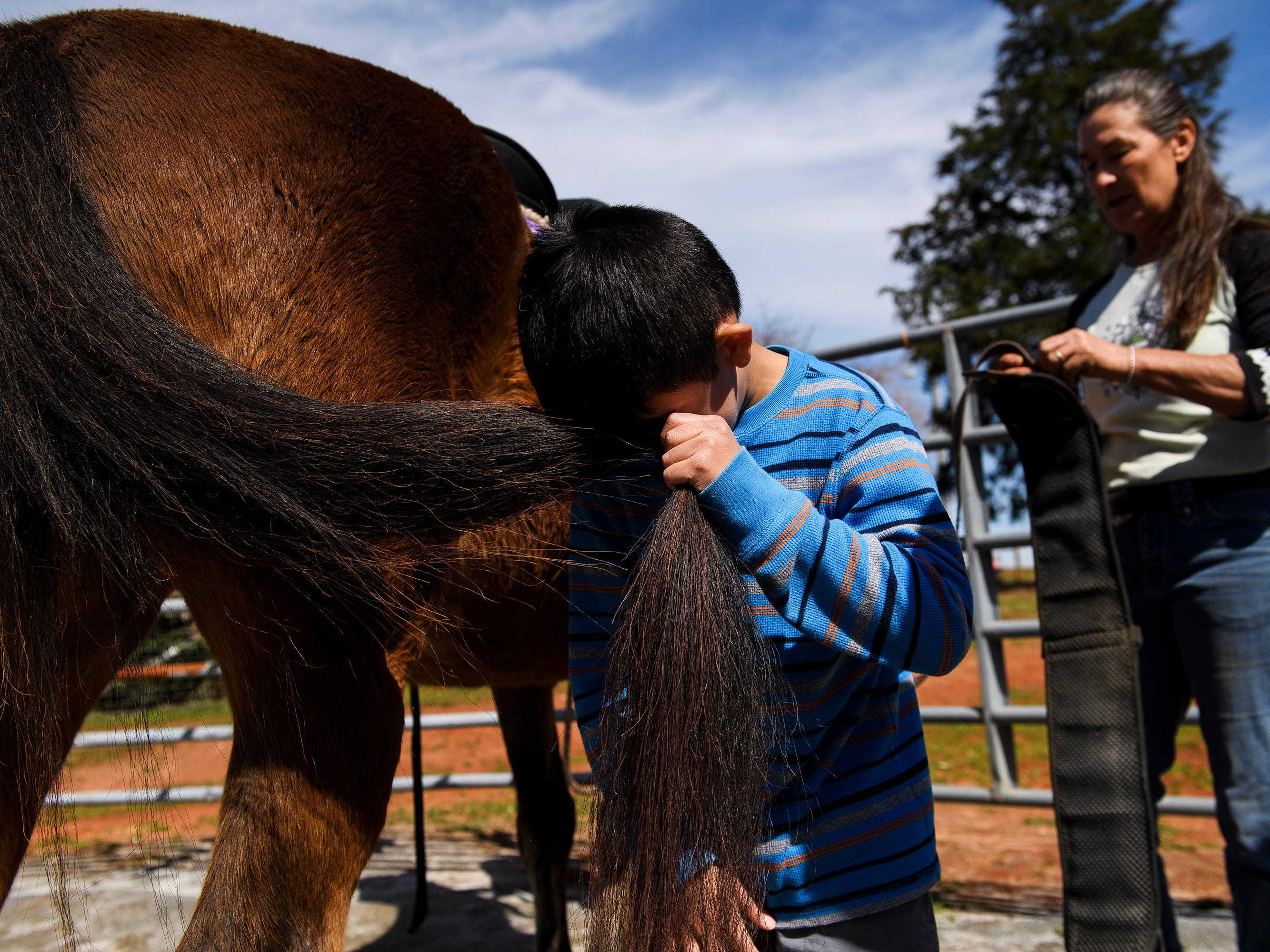 Diego Popa, 9, plays with a horse's tail before beginning his riding lesson at J Rest Farm, Tuesday, March 12, 2019.