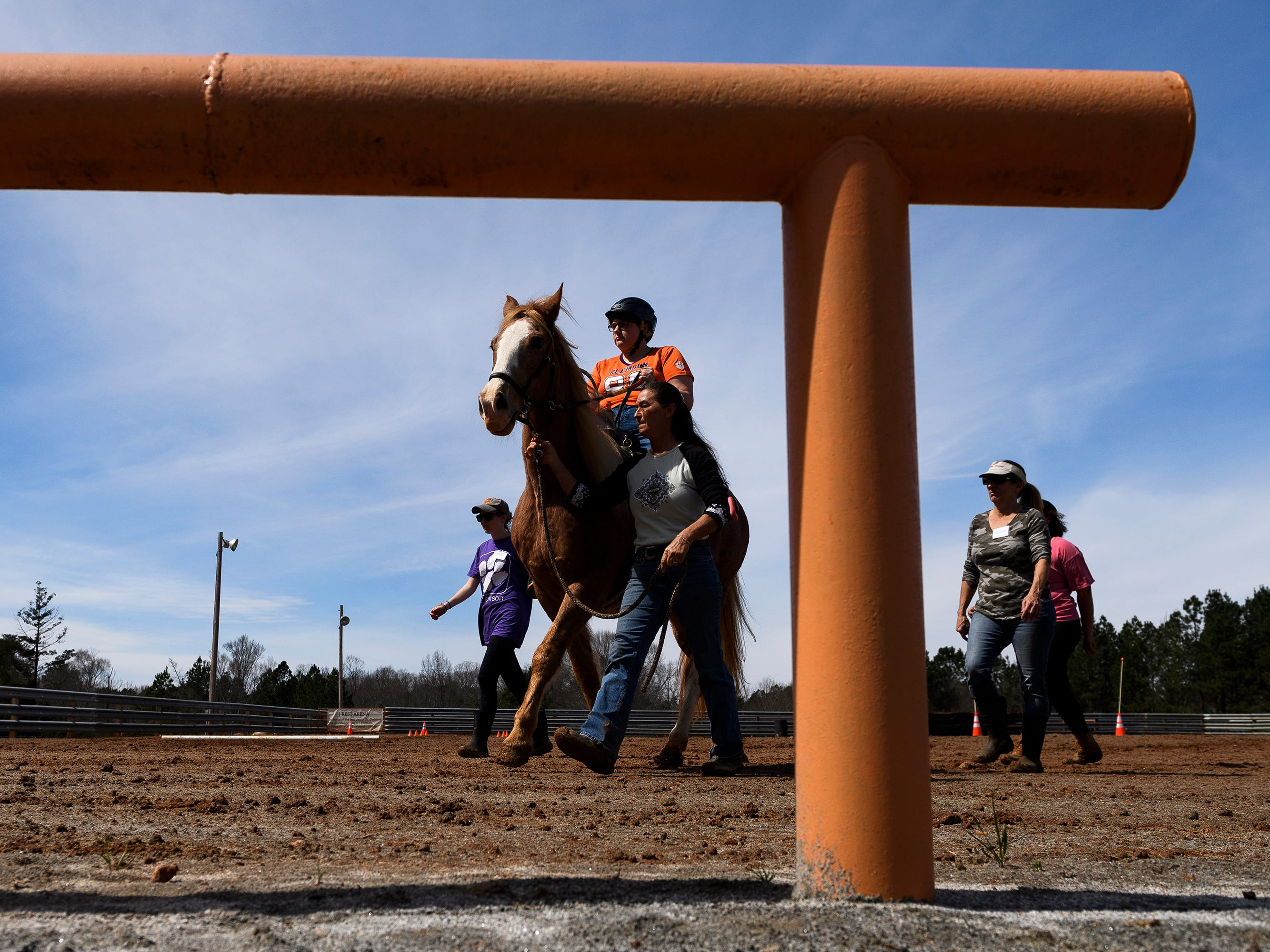 Lisa Hartman and other volunteers walk with Sarah Wright as she rides around the obstacle course at J Rest Farm Tuesday, March 12, 2019.
