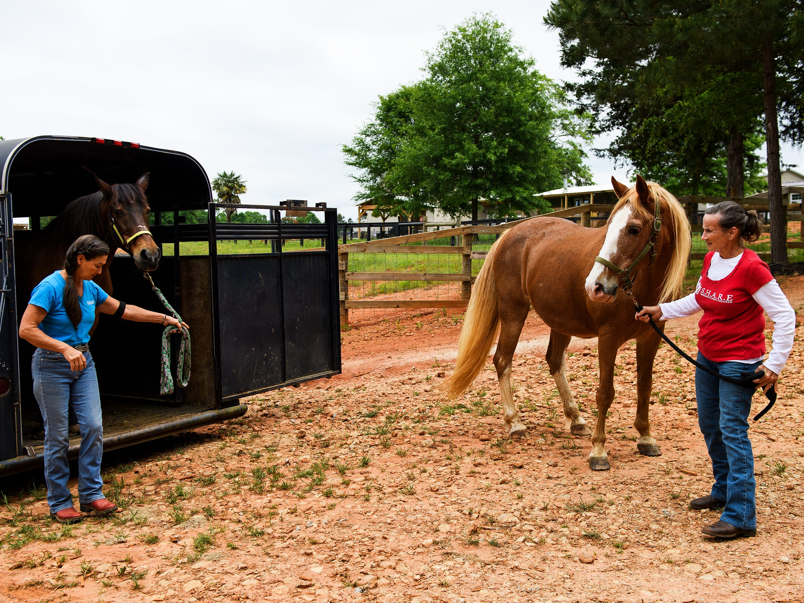 Lisa Hartman and volunteer Darlene Whitmore move horses from the trailer as they prepare for a S.H.A.R.E. riding lesson at J Rest Farm Tuesday, May 7, 2019.