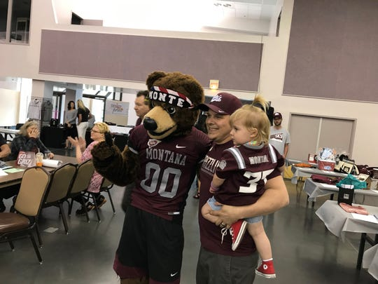 University of Montana mascot Monte poses with Eric Rindal and his daughter McKenna during the Grizzly Coaches Barbecue Tuesday night at the Mansfield Convention Center in Great Falls