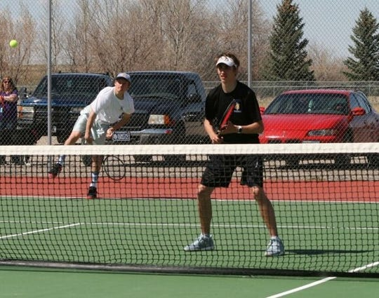 Nick Scott, in white, is serving while teammate Wyatt Walters awaits the return at the net. The Great Falls Central teammates won the divisional doubles' title and will play at the State B-C Tournament this weekend in Bozeman.