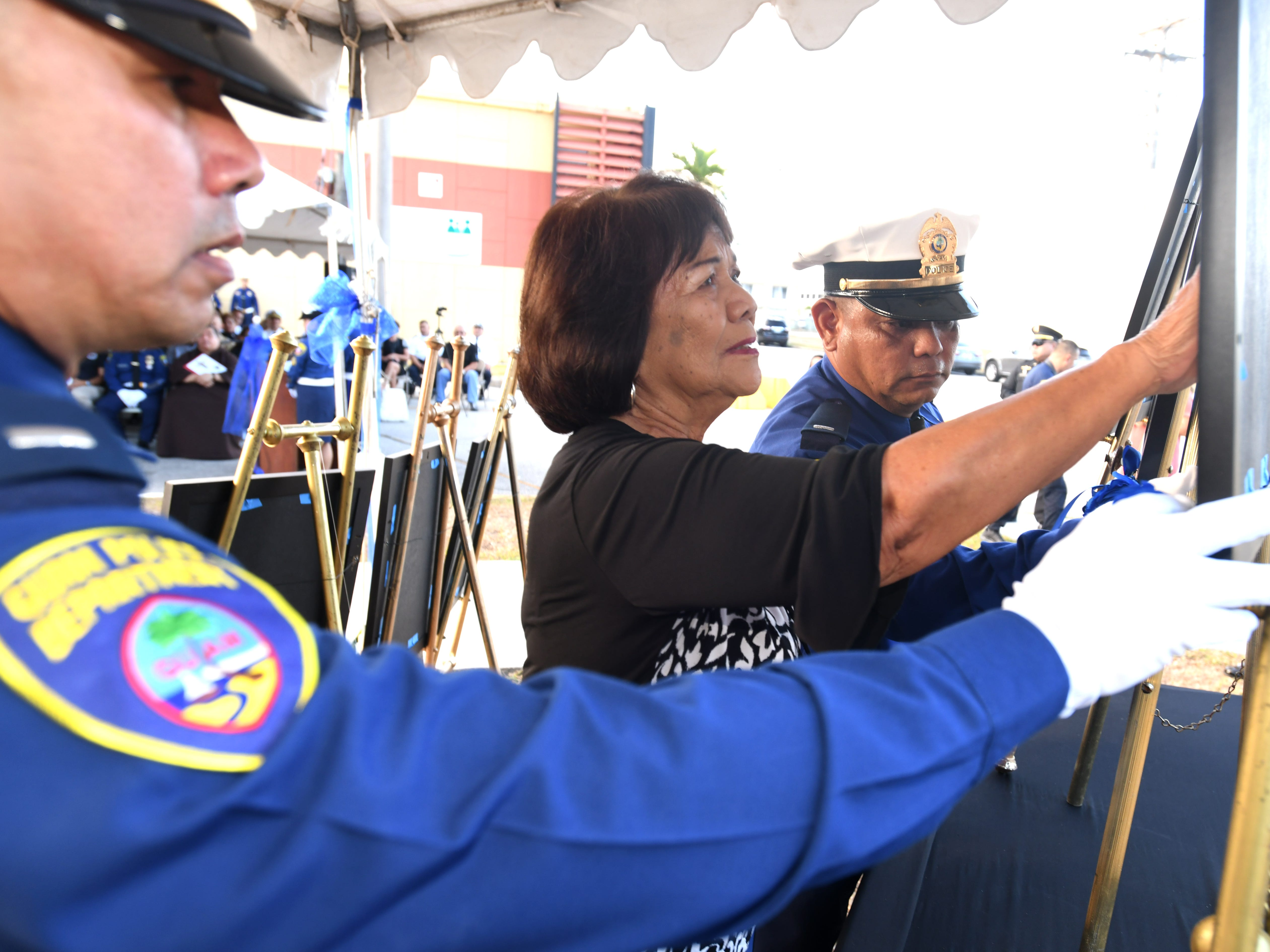 Meding Santos Snyder, center, reaches out to gently touch the photo of her brother, Police Officer Juan Santos, during the Peace Officers' Memorial Service and Wreath Laying Ceremony held at the Guam Police Department's Badge Memorial Park in Hagåtña on Wednesday, May 15, 2019.