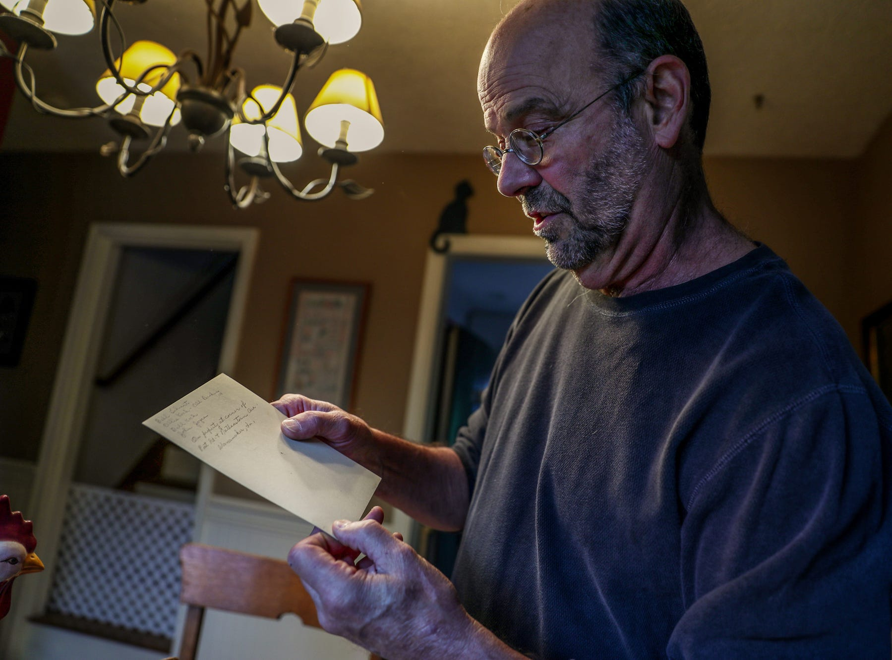 Jeff Purvis reads note from the back of a picture he pulled from a large box of family photos on Thursday, May 2, 2019. The photo is of a family cabin located in Indiana that he believes is no longer standing.