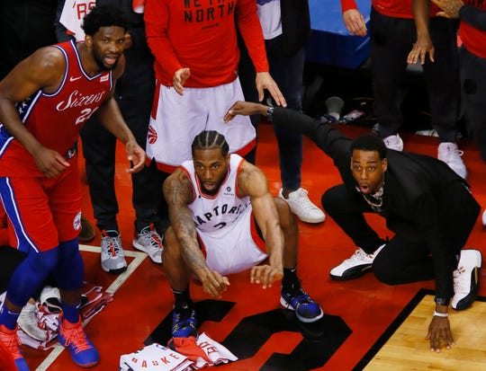 Former UIndy player Jordan Loyd (right) looks on as Raptors forward Kawhi Leonard watches his game winning basket go in against the Philadelphia 76ers during game seven of the second round of the 2019 NBA Playoffs.