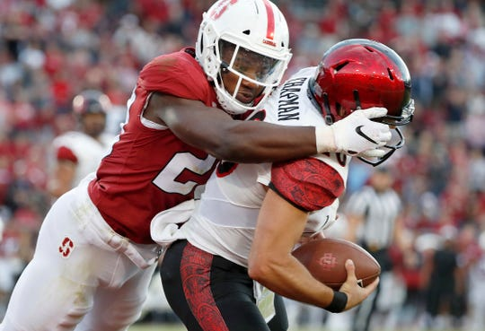 Stanford linebacker Bobby Okereke (20)  tackles San Diego State quarterback Christian Chapman in the end zone for a safety, Aug. 31, 2018, in Stanford, Calif.