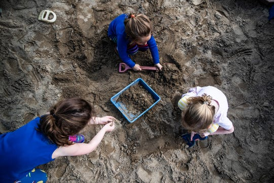 Three pre-kindergarten girls dig in the sand during outside play at IU Health Day Early Learning Center in Indianapolis on Tuesday, May 14, 2019.