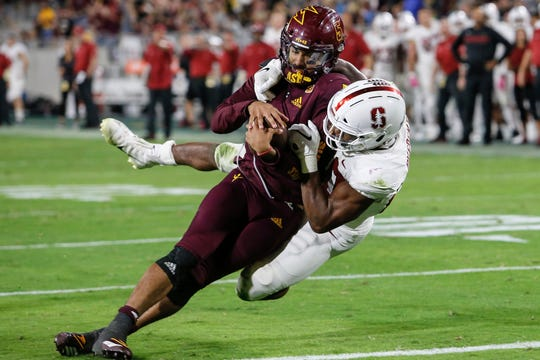 Stanford linebacker Bobby Okereke (20) tries to bring down Arizona State quarterback Manny Wilkins.