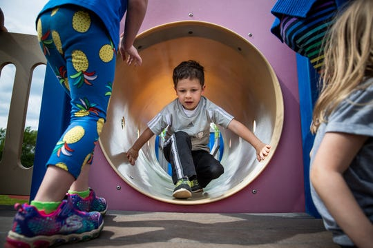 A pre-kindergarten boy take his turn moving through a tunnel during outside play at IU Health Day Early Learning Center in Indianapolis on Tuesday, May 14, 2019.