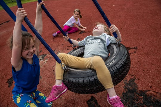 Three pre-kindergarten girls take turns on a tire swing during outside play at IU Health Day Early Learning Center in Indianapolis on Tuesday, May 14, 2019.