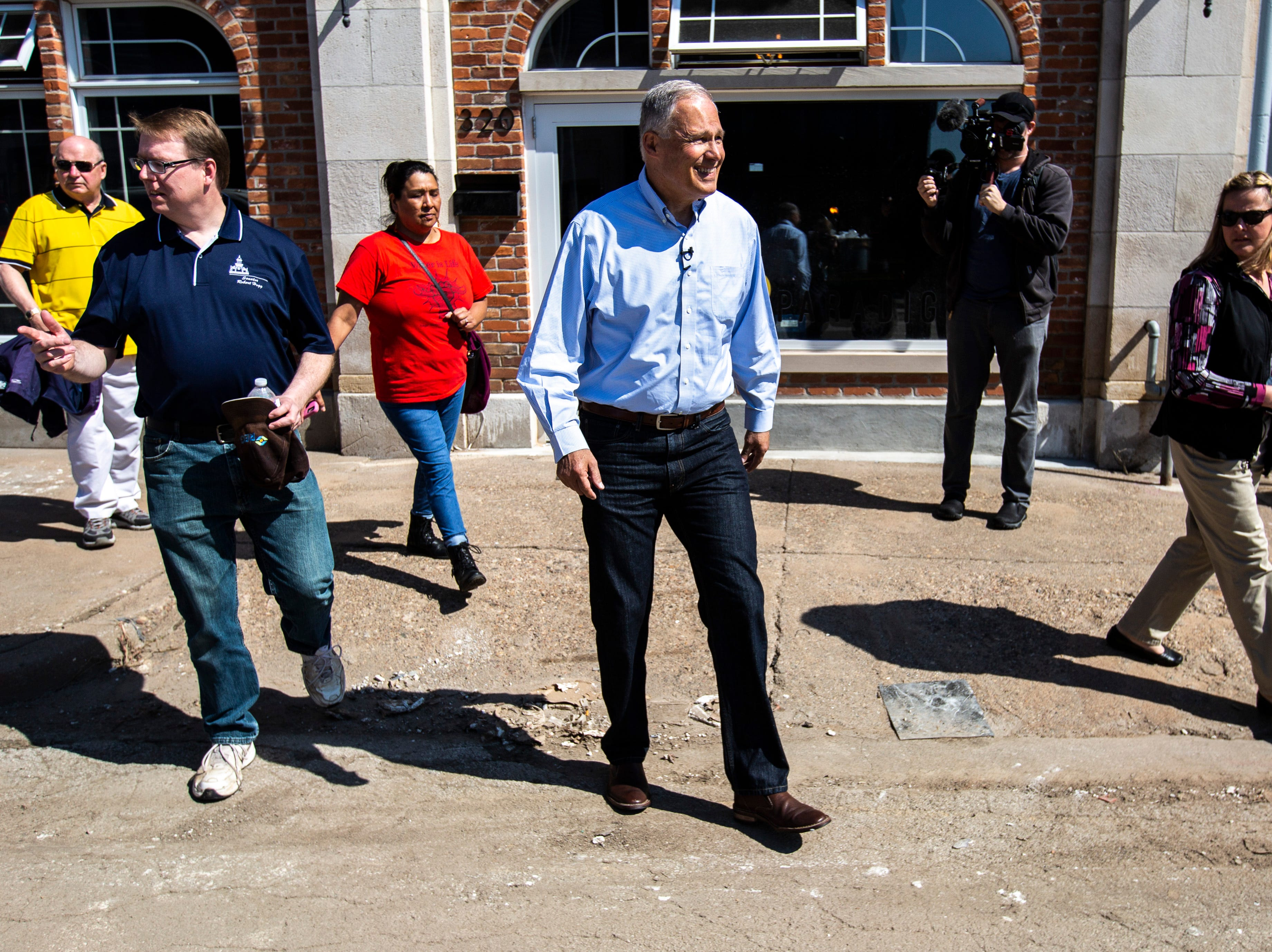 Washington Gov. Jay Inslee tours areas impacted by floodwaters, Wednesday, May 15, 2019, in downtown Davenport, Iowa.
