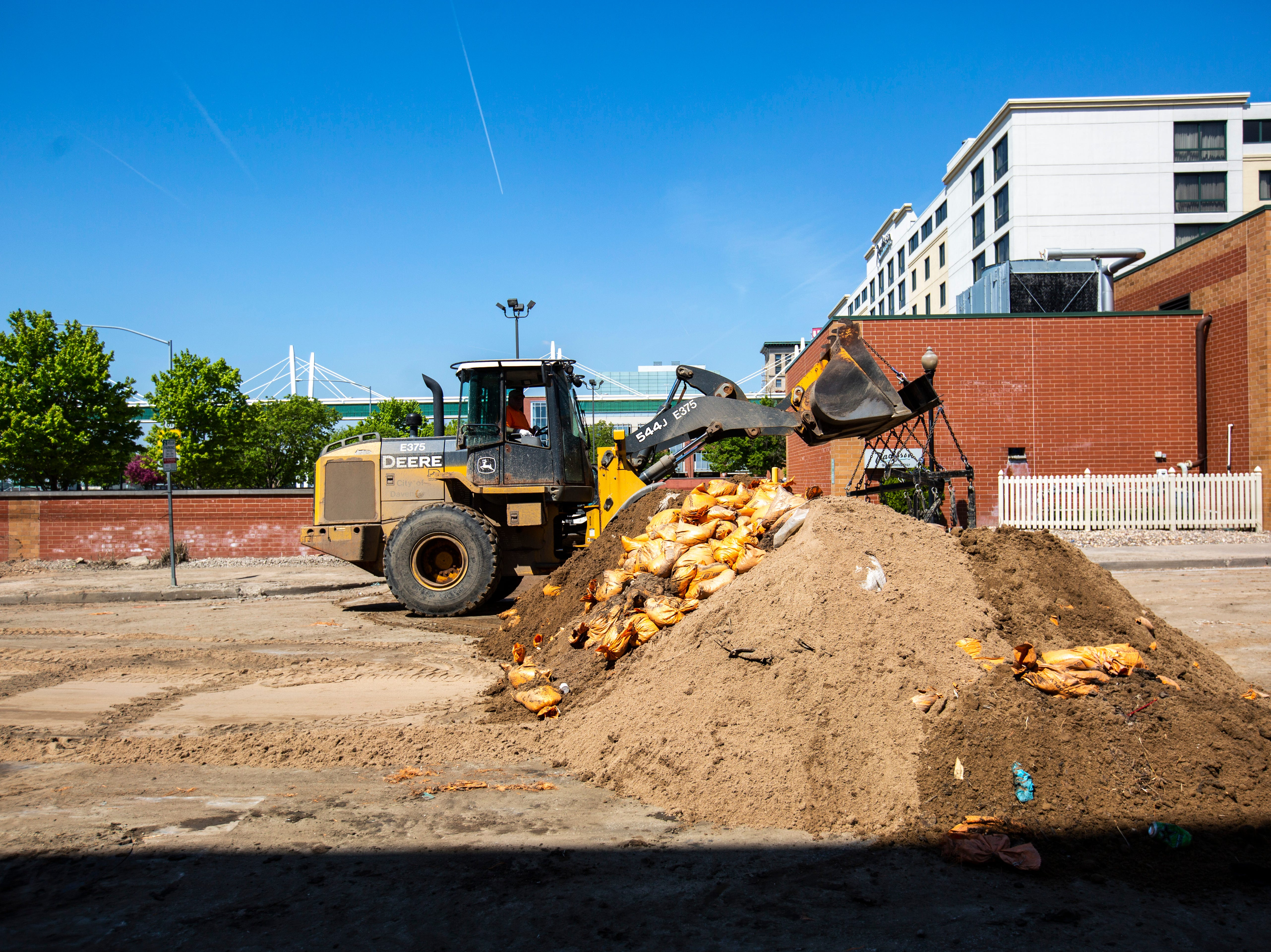 A City of Davenport crew removes a HESCO barrier and sandbags, Wednesday, May 15, 2019, in downtown Davenport, Iowa.