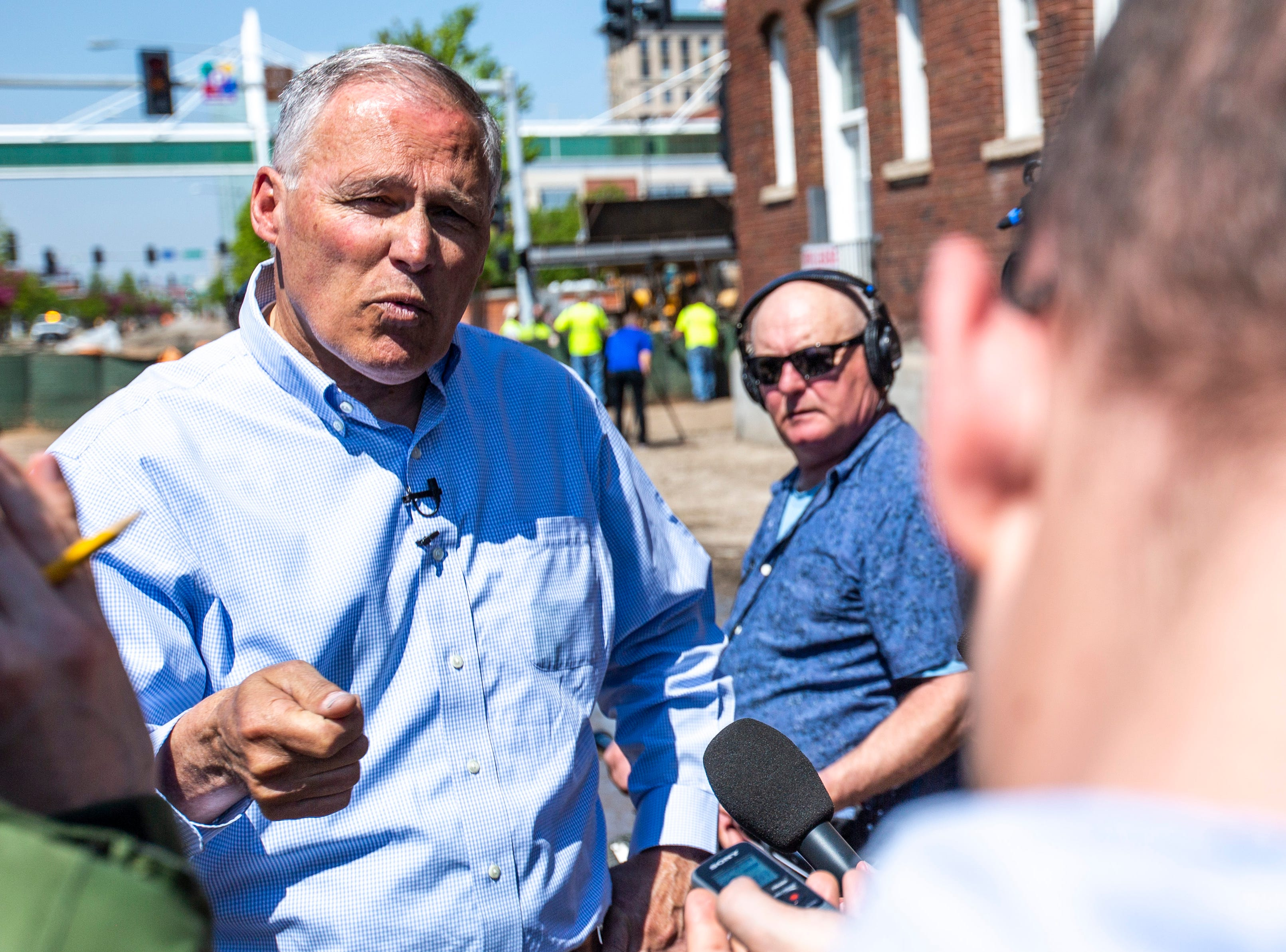 Washington Gov. Jay Inslee talks with reporters after touring areas impacted by floodwaters, Wednesday, May 15, 2019, in downtown Davenport, Iowa.