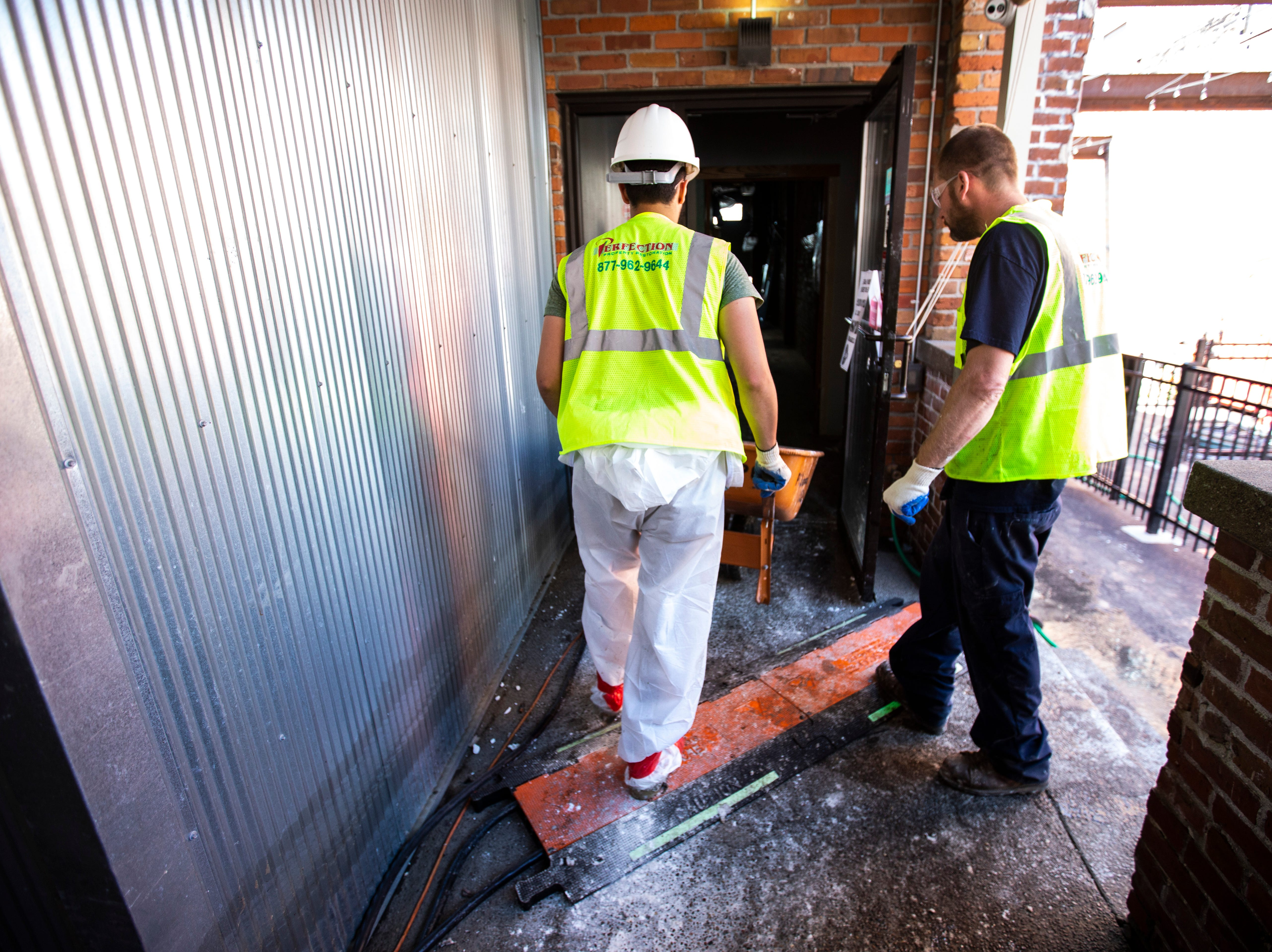 Workers clear out debris the remained after floodwater receded, Wednesday, May 15, 2019, at Front Street Brewery in downtown Davenport, Iowa.
