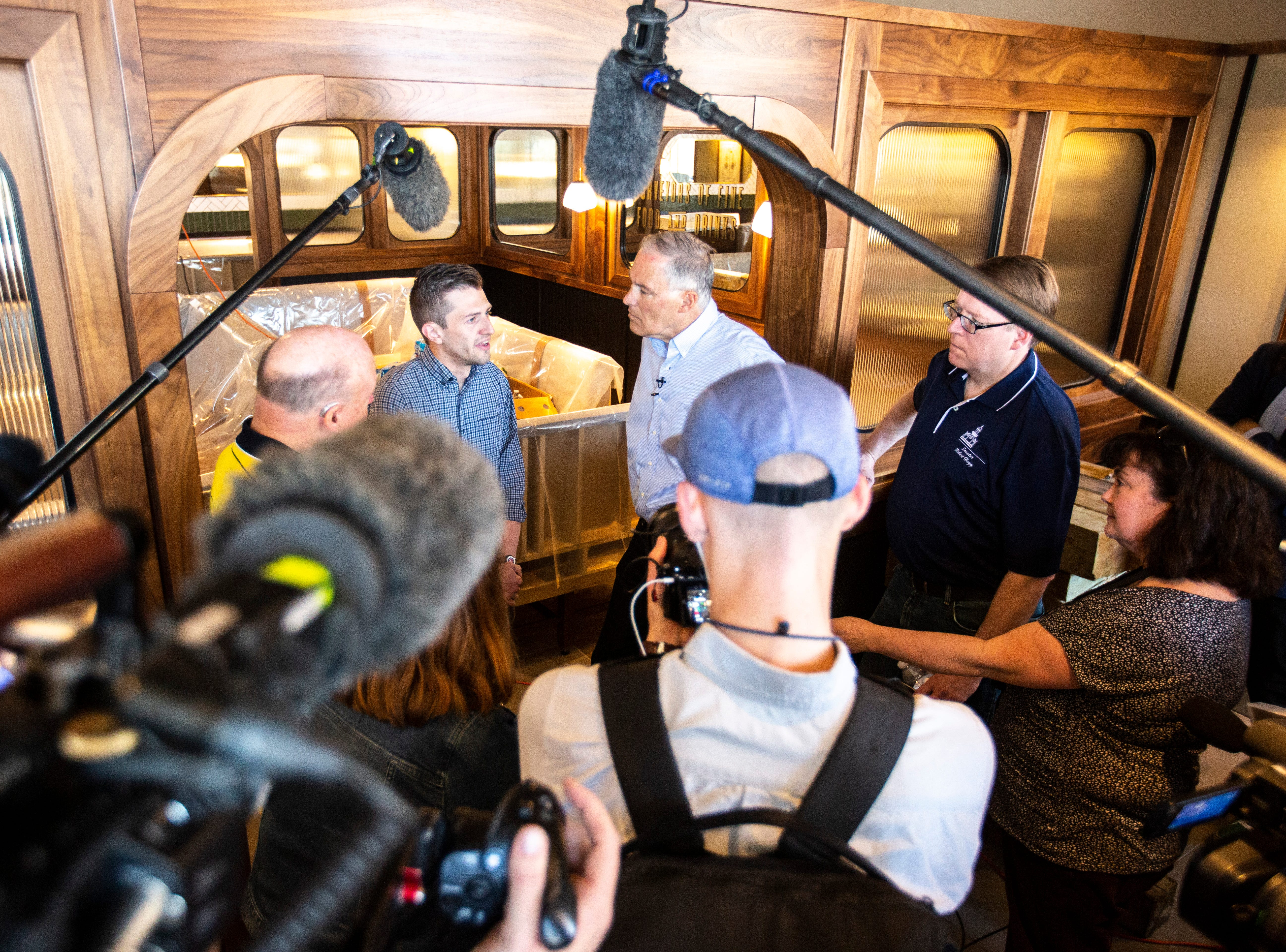 Washington Gov. Jay Inslee talks with The Half Nelson owner Matt Osborn, left, while touring areas impacted by floodwaters, Wednesday, May 15, 2019, in downtown Davenport, Iowa. Osborn's business was set to open the day a temporary flood wall barrier broke.