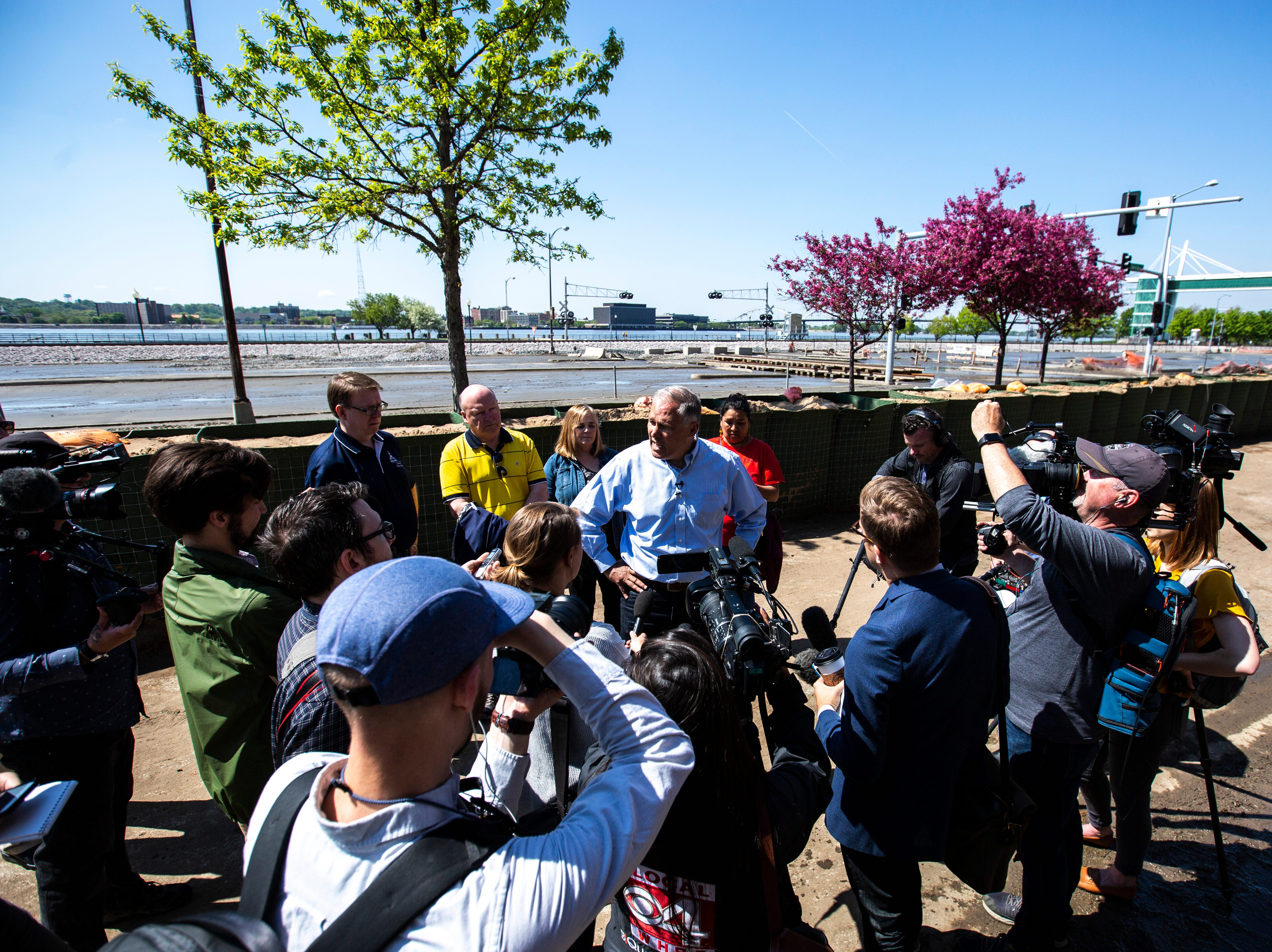 Washington Gov. Jay Inslee speaks with reporters after touring areas impacted by floodwaters, Wednesday, May 15, 2019, in downtown Davenport, Iowa.