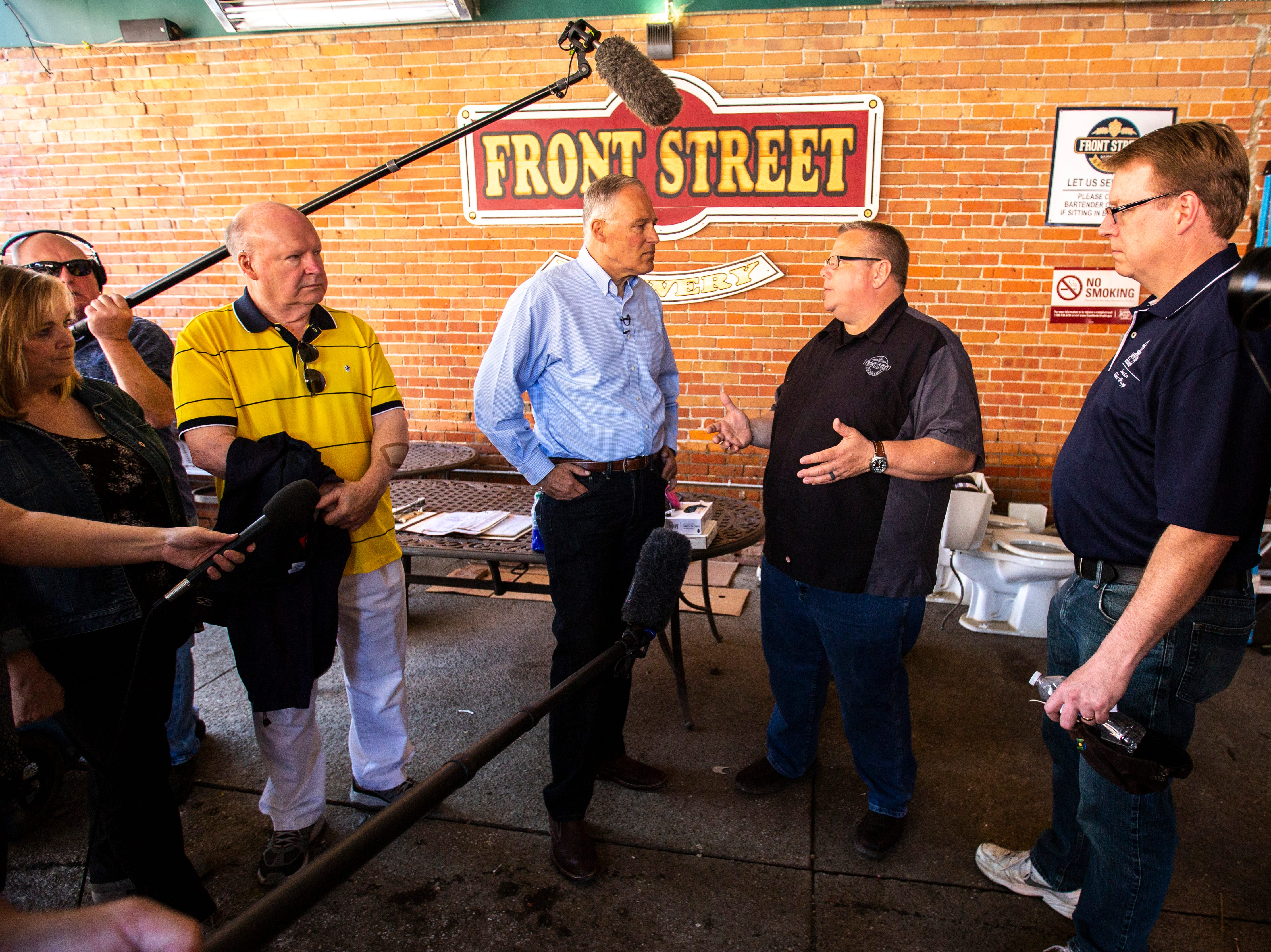 Washington Gov. Jay Inslee talks with Front Street Brewery owner Tim Baldwin while touring areas impacted by floodwaters, Wednesday, May 15, 2019, in downtown Davenport, Iowa.