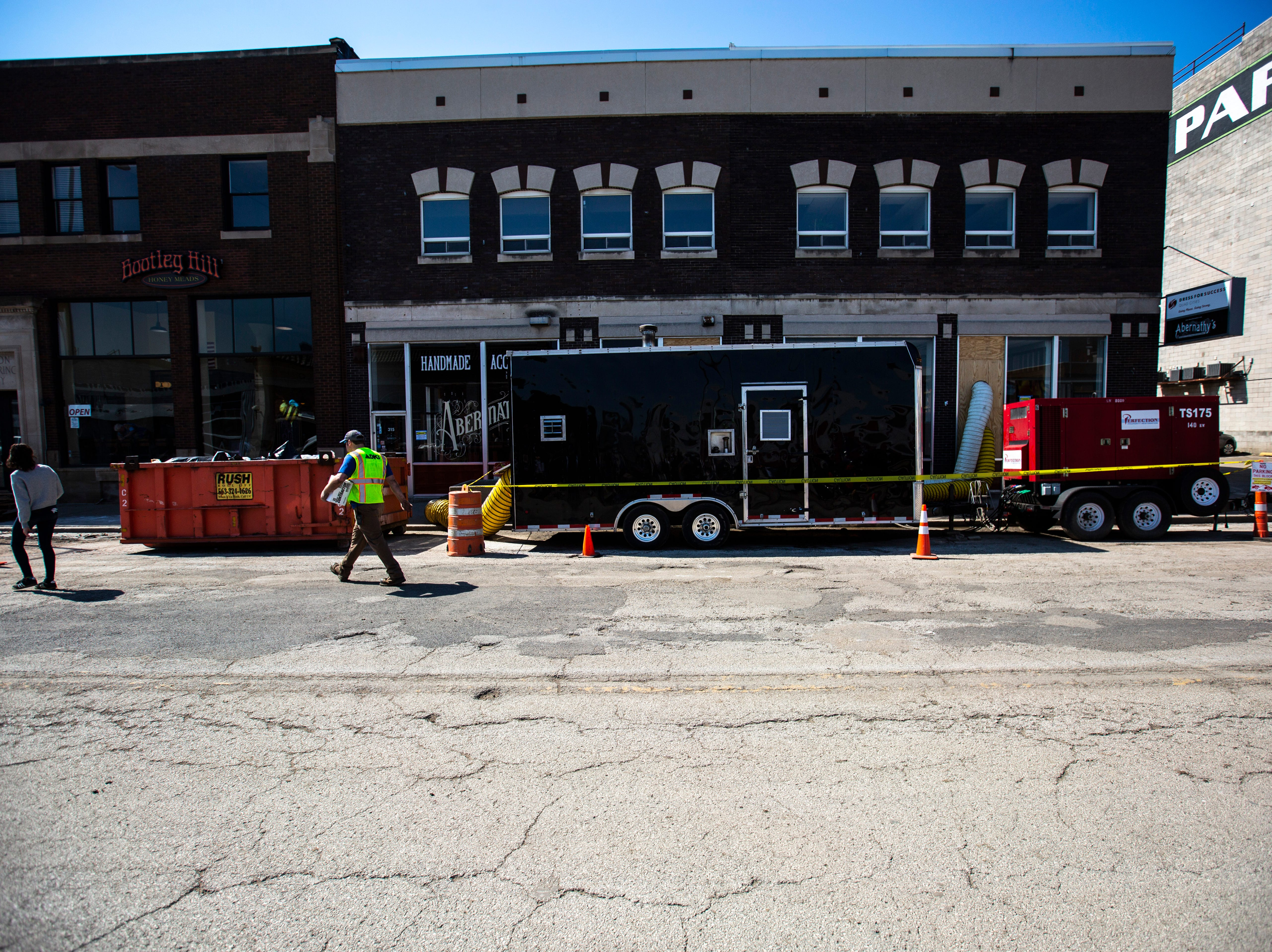 People walk along 2nd Street as cleanup begins after floodwaters receded, Wednesday, May 15, 2019, in downtown Davenport, Iowa.