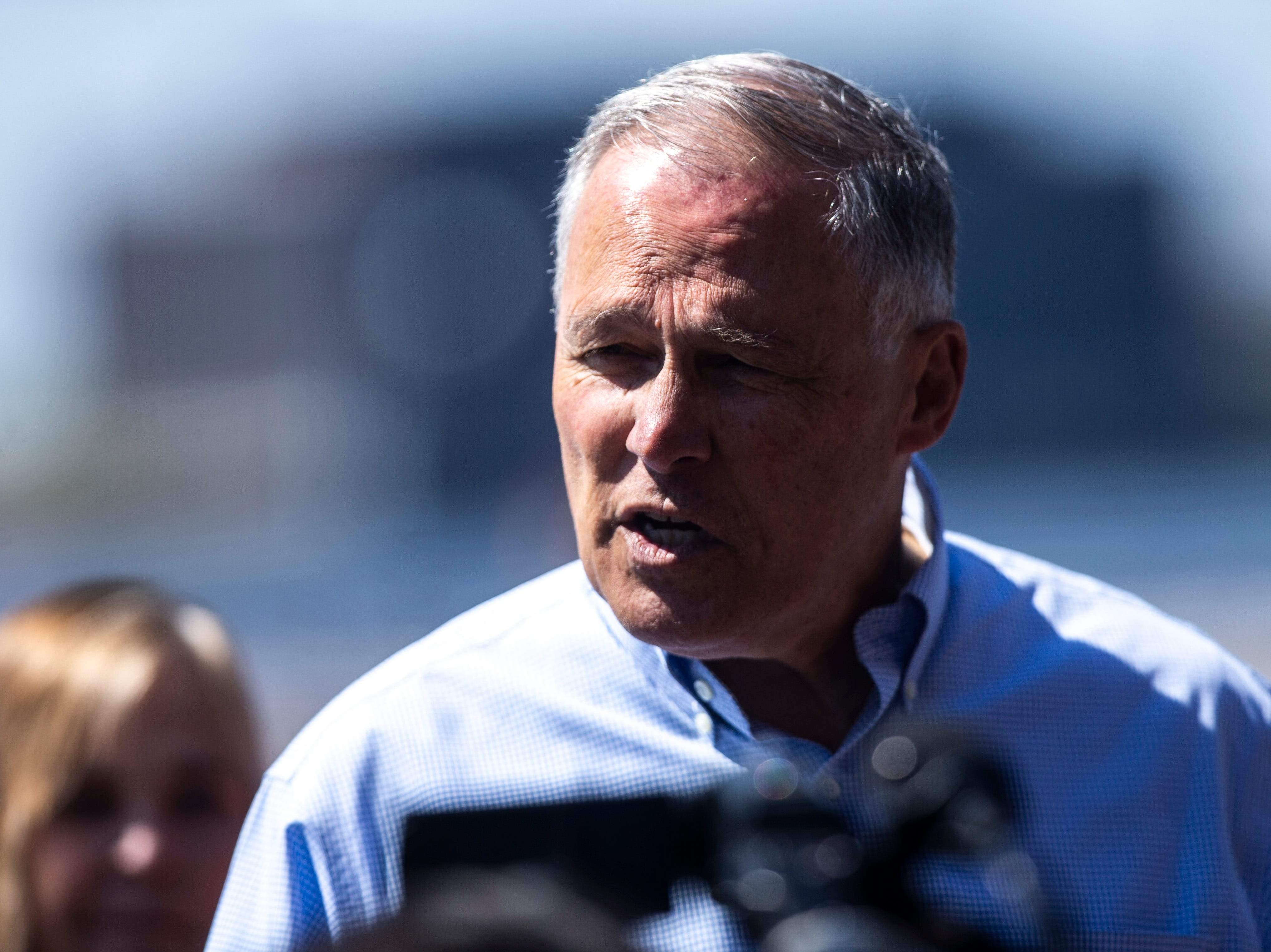 Washington Gov. Jay Inslee speaks to reporters after touring areas impacted by floodwaters, Wednesday, May 15, 2019, in downtown Davenport, Iowa.