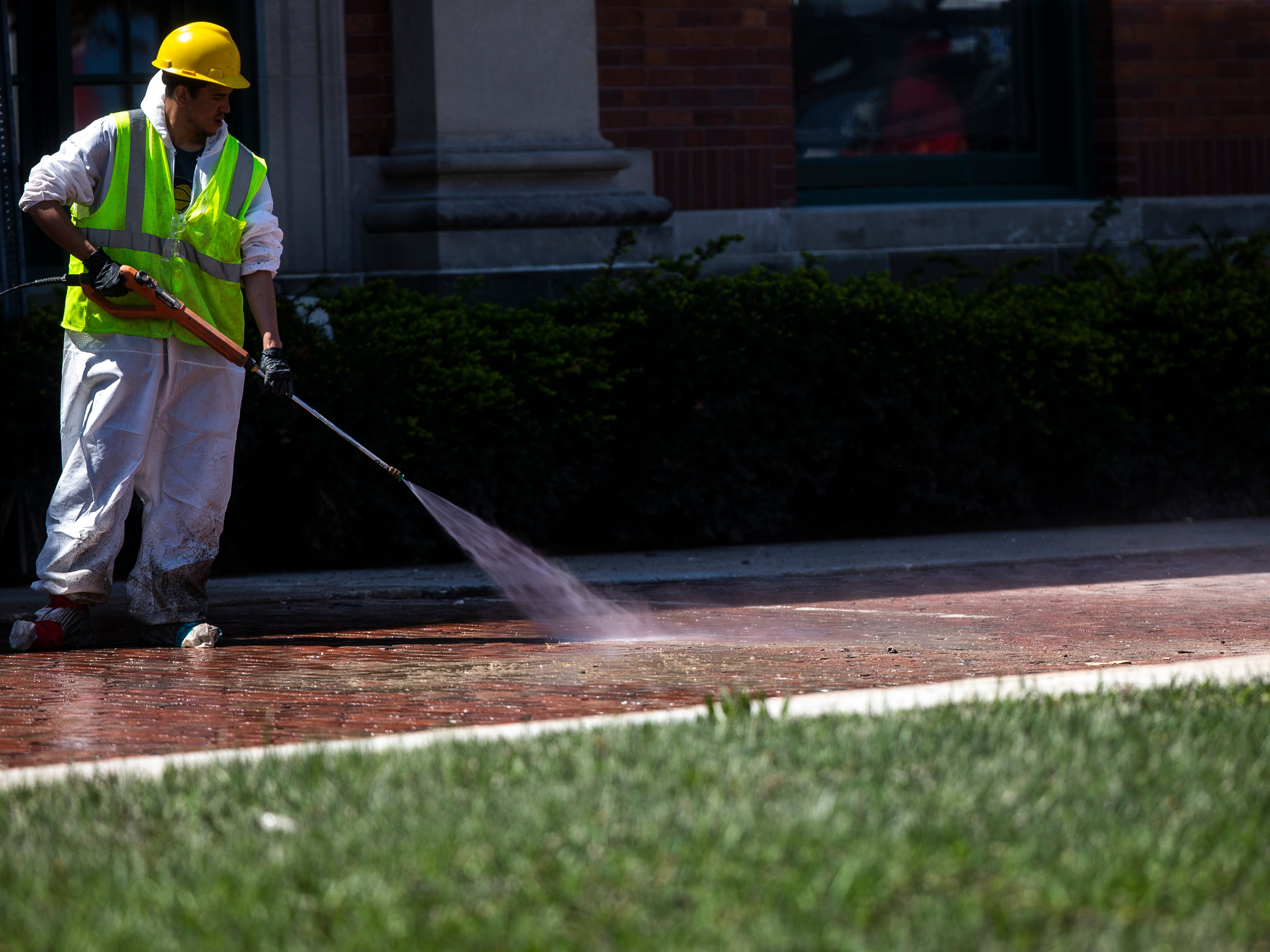 A worker power washes debris off of bricks as cleanup begins after floodwaters receded, Wednesday, May 15, 2019, along River Drive in downtown Davenport, Iowa.