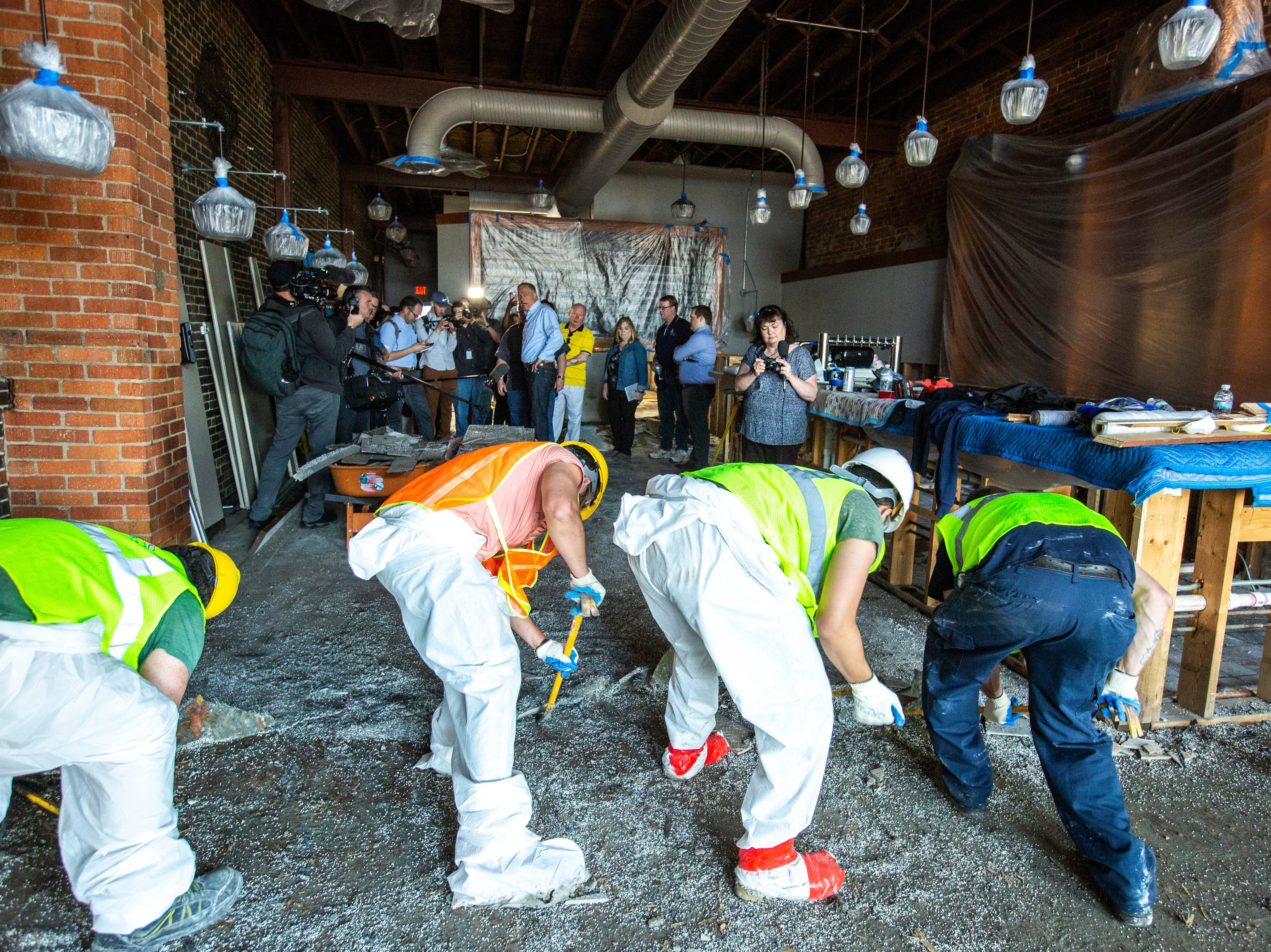 Washington Gov. Jay Inslee tours areas impacted by floodwaters while workers chip away at a subfloor, Wednesday, May 15, 2019, inside Front Street Brewery in downtown Davenport, Iowa.