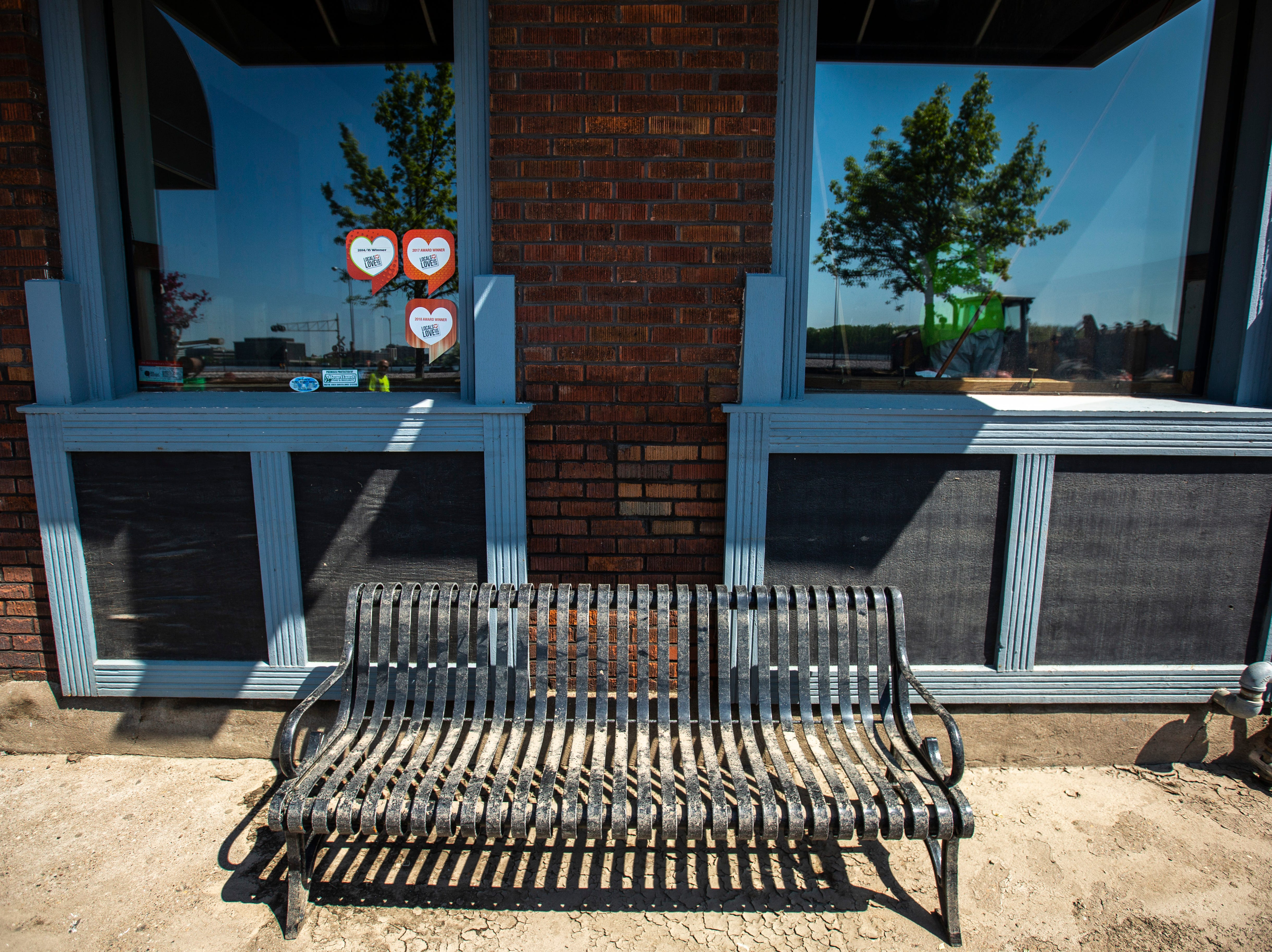 A bench in front of Front Street Brewery shows the remains of debris as cleanup begins after floodwaters receded, Wednesday, May 15, 2019, in downtown Davenport, Iowa.